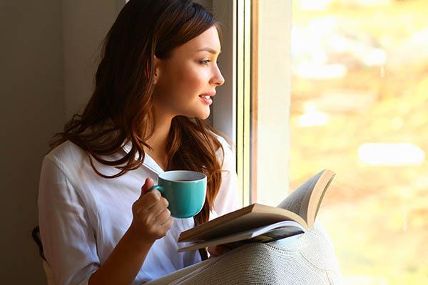 woman relaxed coffee near window panic atatcks mfine